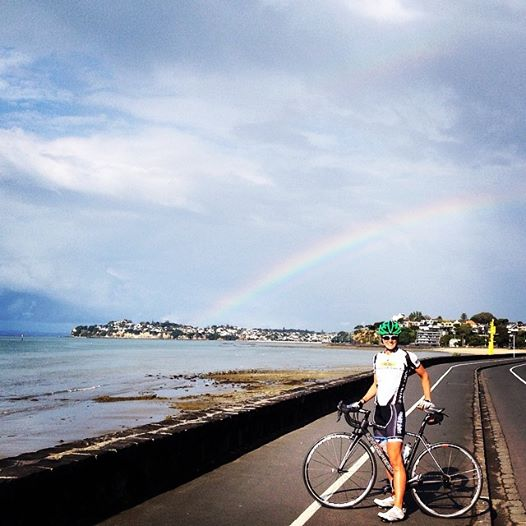 Katie rainbow on bike NZ